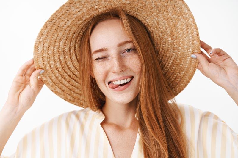 Mujer sonriendo y guiñamndo un ojo con un sombrero