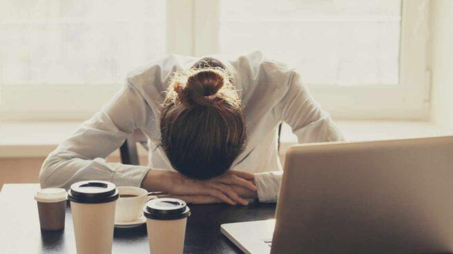 Mujer agotada con cabeza en mesa de oficina y varios cafés en la mesa